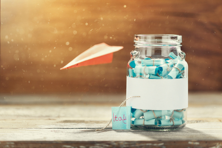Glass jar with list of countries to visit and paper airplane.