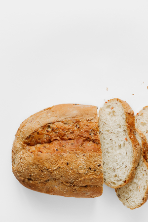Loaf bread with slices bread on white  with copy space top view