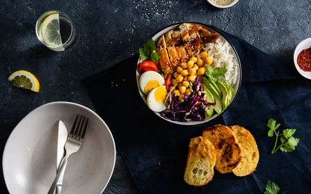 Dinner table with buddha bowl. Rice, chickpeas with chicken breast, eggs and vegetables top view
