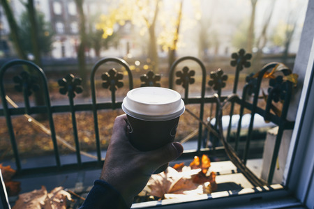 Male hand holding cup of coffee in the morning sun against the window