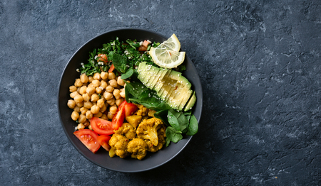 Buddha bowl. Vegetarian healthy balanced food. Aloo gobi, chickpeas, tomato, avocado, tabule salad and spinach Standard-Bild