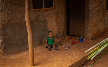 Zanzibar, Tanzania, Africa - February 3, 2017: Cute African baby laughs sitting on the porch of clay hut