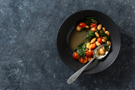 Dinner bowl of stewed white beans with vegetables on a dark background top view Stock Photo