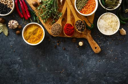 Épices, herbes, riz et divers haricots et assaisonnements pour la cuisson sur fond sombre avec vue de dessus de l'espace de copie