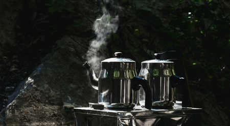 Camping camp holidays concept. Two teapots with hot tea