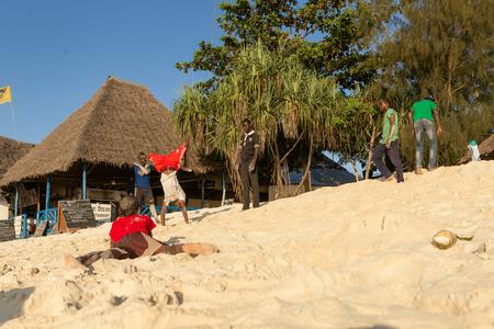 Zanzibar, Tanzania, Africa - February 3, 2017: Cheerful African teenagers fooling around on the beach