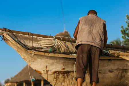 Poor African fisherman repairing his old wooden boat on the ocean