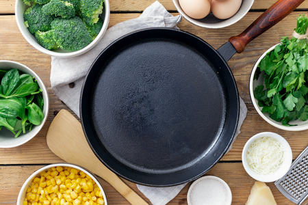 Empty cooking pan with ingredients for cooking healthy breakfast eggs with broccoli, spinach and cheese on wooden table top view Stock fotó