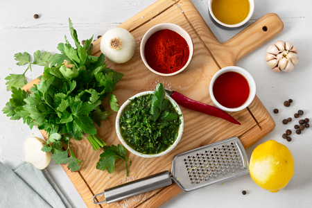 Raw ingredients for preparation Argentinian green Chimichurri or Chimmichurri salsa or sauce on white wooden table Stockfoto