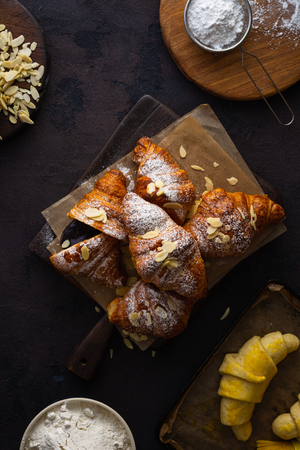 Fresh croissants with almond flakes and icing sugar top view