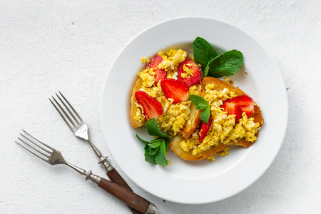 Sandwiches with scrambled eggs and strawberry. Delicious breakfast or snack