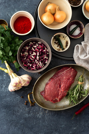 Raw ingredients for cooking healthy food. Raw beef meat with herbs, spices and beans top view