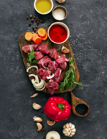 Sliced beef fillet with vegetable. kitchen table with сuts meat and veggies on dark table top view. Ingredients cooking meat Reklamní fotografie