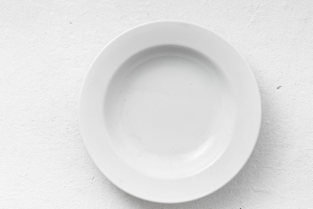 Empty white round plate on a white