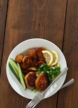 Plate of food. Fresh vegetarian cutlets with new potatoes and salad on a wooden table copy space top view