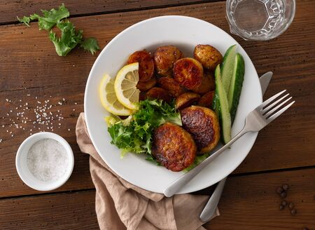 Dinner table with plate food. Fresh vegetarian cutlets with new potatoes and salad top view Stock Photo