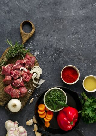 Sliced beef fillet with vegetable. kitchen table with сuts meat and veggies on dark table top view. Ingredients cooking meat Stock Photo