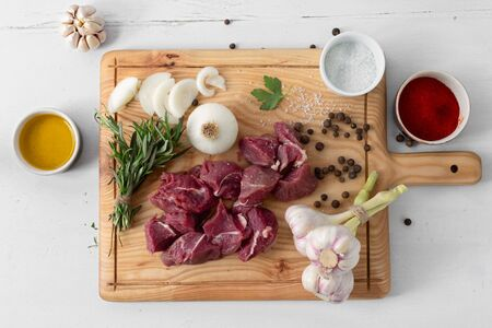 Raw meat and vegetables on white wooden background top view. Cooking beef meat Stock Photo