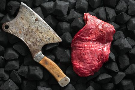 Raw fresh beef meat with old butcher knife over a charcoal top view