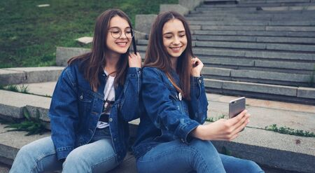 Two happy young best friends using social media on their smartphone Stock Photo