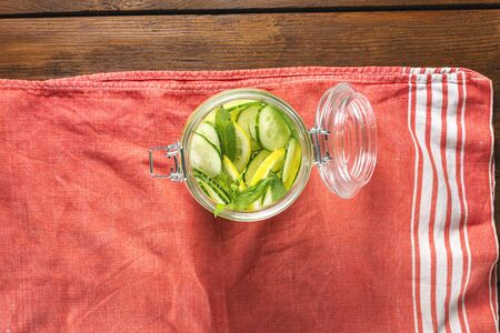 Detox drink cucumber water in the glass on wooden table top view