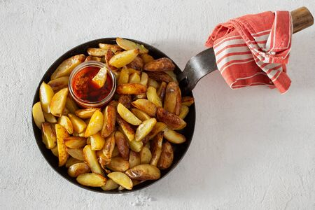 Fresh fried potatoes with brava sauce on a white background top view