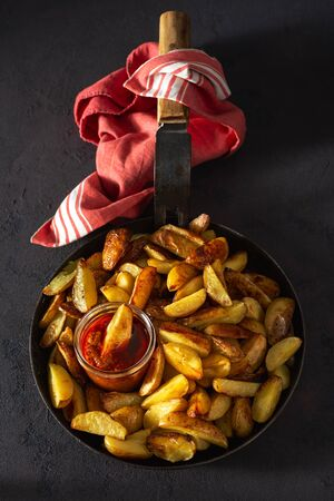 Fresh fried potatoes with  brava sauce on a dark background top view