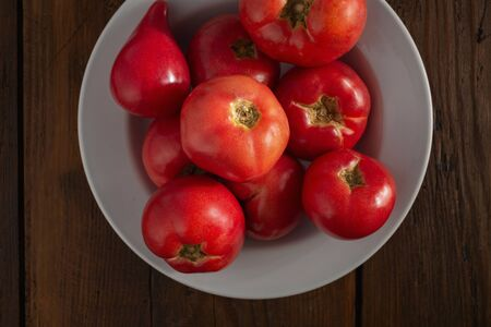 Fresh red tomatoes on a wooden background top view