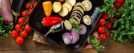 Raw vegetables for cooking on a grill pan on a wooden  top view