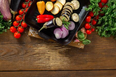 Various vegetables for cooking on a grill pan on a wooden  top view copy space