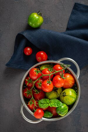 Set of different fresh washed homemade tomatoes with basil leaves on a dark  in a sieve
