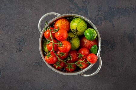 Overhead view fresh tomatoes with basil leaves on a dark  in sieve