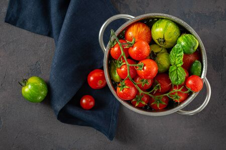 Fresh tomatoes with basil leaves on a dark  in sieve