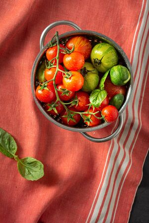 Overhead view fresh tomatoes with basil leaves in sieve Stock Photo