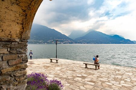 Mother with daughter sits on a bench near Lake Como Italy