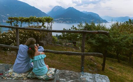 Mother with daughter enjoy sunset near Lake Como. Italy