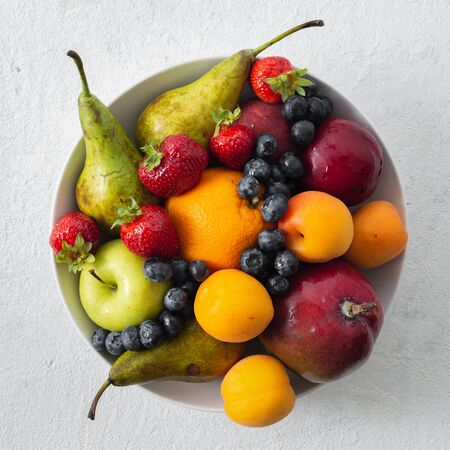 Mix fruits plate on a light background top view