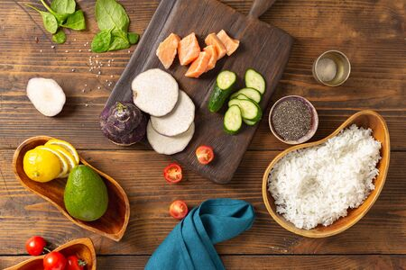 Ingredients for preparation poke bowl with salmon, avocado, vegetables and chia seeds on wooden background top view