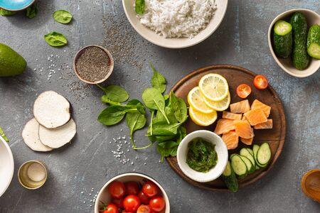 Concetto di cibo dietetico sano Ingredienti per cucinare poke bowl con salmone, avocado, verdure e semi di chia vista dall'alto