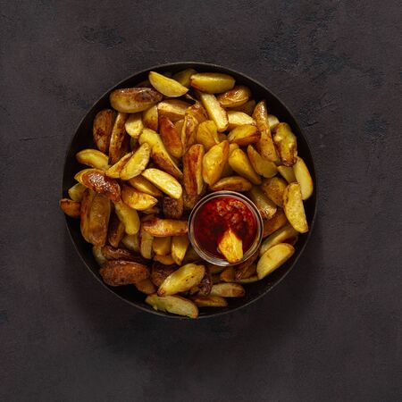 Fried potatoes with  brava sauce on a dark background with copy space top view Фото со стока