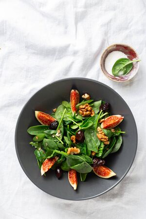 Healthy breakfast, appetizer, snack. Salad of figs, walnut, smoked olives and spinach on white background top view