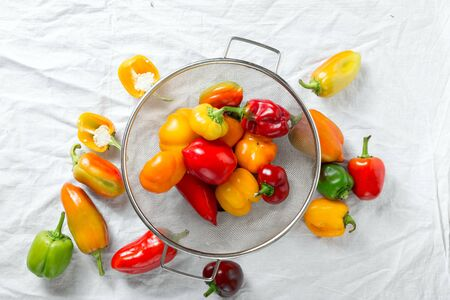 Washed yellow, red and green bell peppers in sieve on white background top view