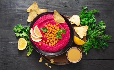 Beetroot hummus in a plate on a dark background top view Stock Photo