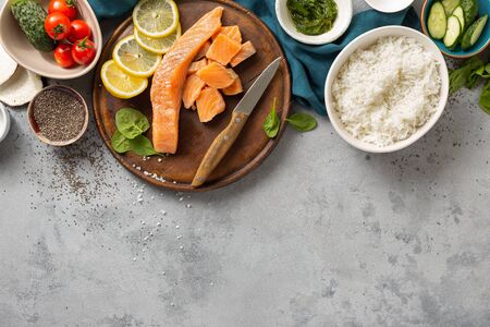 Tasty and healthy food concept. Ingredients for cooking poke bowl with salmon, avocado, vegetables and chia seeds top view copy space