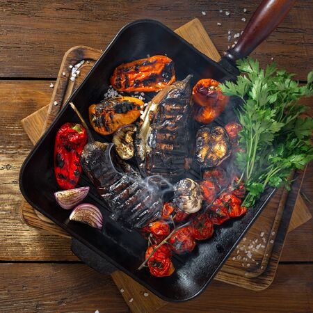 Various vegetables cooked on a grill pan on a wooden background top view Фото со стока