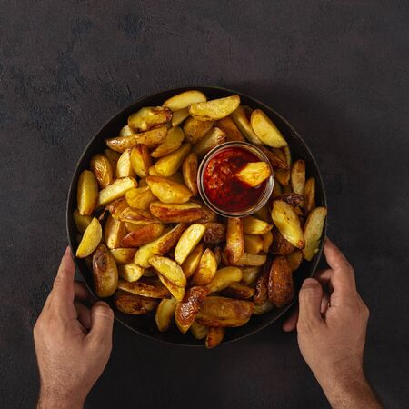 Male hands holding a pan with fresh fried potatoes