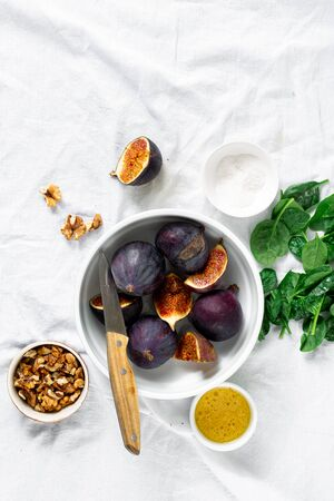 Ingredients for cooking vegetarian salad of figs, nuts and spinach top view Фото со стока