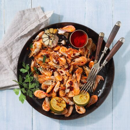 Fresh fried prawns on a blue wooden background top view