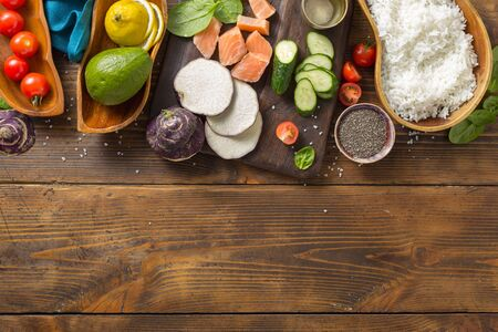Ingredients for preparation poke bowl with salmon, avocado, vegetables and chia seeds on wooden background top view copy space