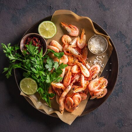 Raw shrimp in a pan with ingredients for cooking on a dark background top view